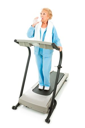 Fit senior woman working out on a treadmill, taking a break to stay hydrated. Stock Photo - 5413109