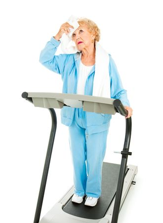Senior lady on a treadmill mops sweat from her forehead with a towel.  She doesnt like working out.  Isolated. photo