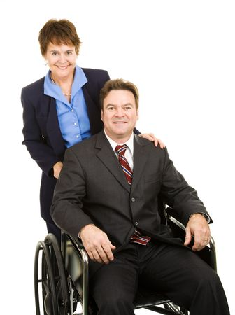 Disabled businessman in a wheelchair, pushed by a female partner or assistant.  Isolated on white. photo