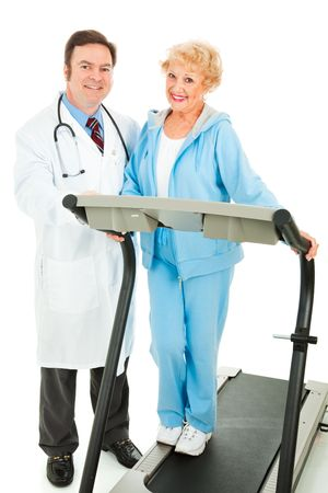 Healthy senior woman on a treadmill, standing beside her doctor.  Isolated on white. Stock Photo - 5439532