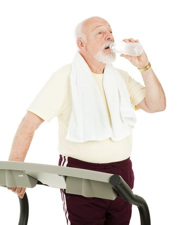 Senior man on treadmill takes a break to drink from a water bottle.  Isolated on white.