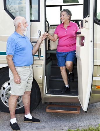Polite senior man helps his wife down the stairs of their motor home.   版權商用圖片