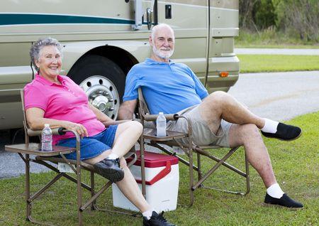 Senior paar op vakantie, ontspannen buiten hun camper. Stockfoto