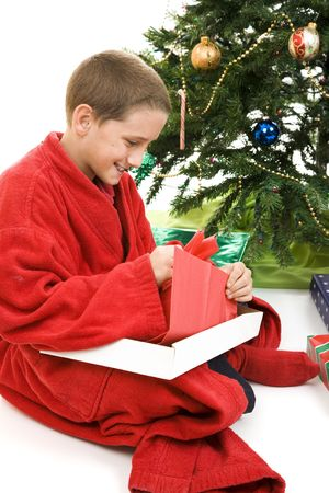 Little boy opening a gift under the tree on Christmas morning.