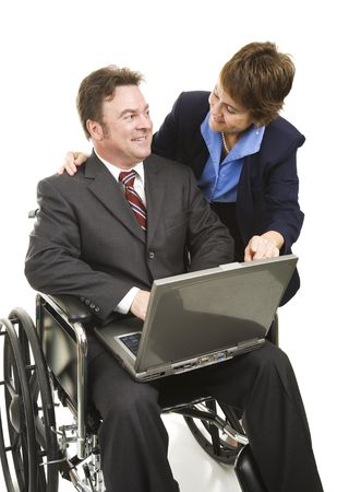Disabled businessman uses a laptop computer with the help of a colleague.  Isolated on white. photo