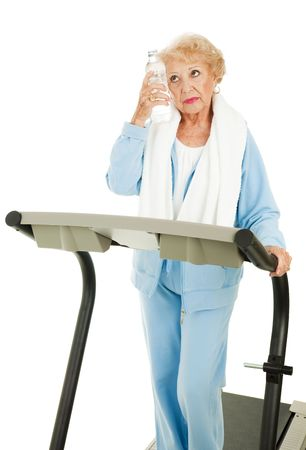 Senior woman on a treadmill cools down with bottled water.  Isolated on white. Stock Photo - 5508329