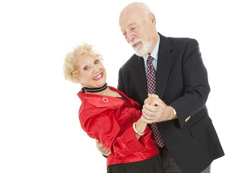 Senior man dips his beautiful wife as they enjoy a dance together.  Isolated on white.