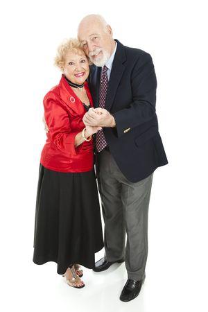 Beautiful senior couple dancing cheek to cheek.  Full body isolated on white.