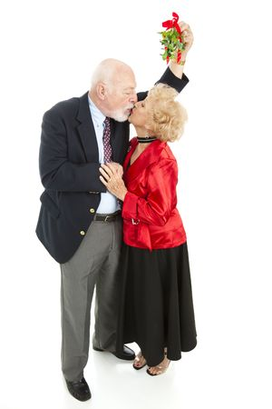 Senior man kisses his beautiful wife under the mistletoe.  Full body isolated on white.