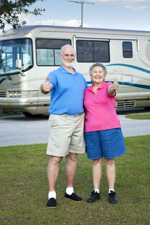 Senior couple in front of their luxury RV, giving thumbs up sign.   photo
