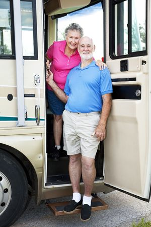 Senior couple posing in the door of their luxury RV.   photo