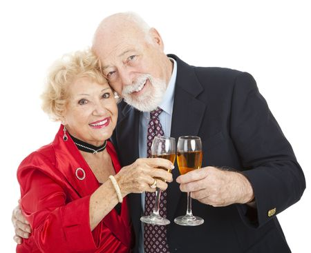 Beautiful senior couple toasting with glasses of champagne.  Isolated on white. photo