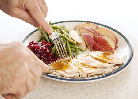 Man's hands eating a delicious turkey dinner for Thanksgiving or other meal.   Stock Photo - 5550523