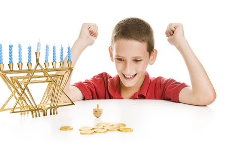 Cute little boy on Chanukah playing with his dreidel.  Isolated on white with menorah and gelt.   photo