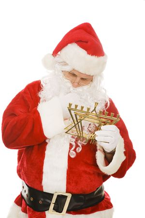 Confused Santa Claus looking at a Chanukah menorah.  Isolated on white.