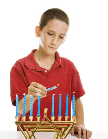 Little boy uses the shamash candle to light the menorah.  Isolated on white.   photo