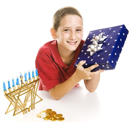 gelt: Adorable little boy with a Chanukah gift, menorah, dreidel and gelt.  Isolated on white.