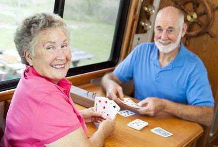 games hand: Happy retired couple playing cards in their motor home.   Stock Photo