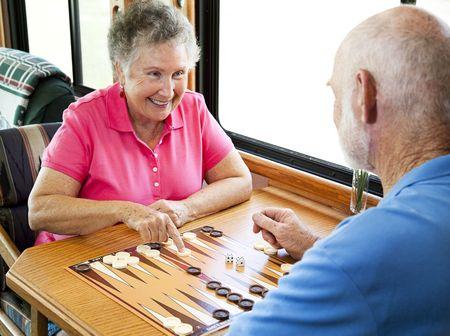 Senior couple enjoys a game of backgammon in their motor home.   Stock Photo