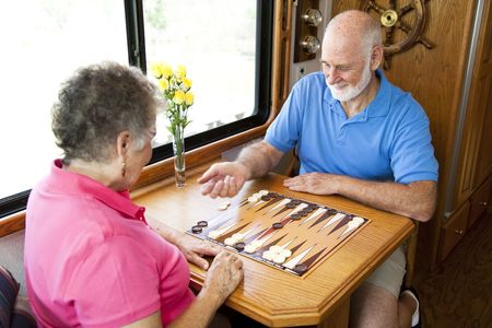 Senior couple on vacation playing backgammon in their motor home.  Motion blur on the mans hand as he shakes the dice.