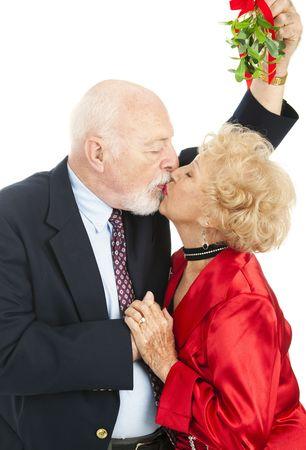 muerdago: Senior couple beso bajo el mu�rdago de Navidad. Fondo blanco.