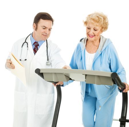 Doctor supervising a fit senior woman as she works out on a treadmill.  Isolated on white. photo