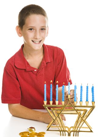 Little boy celebrates Chanukah by lighting the candles on his menorah.  Isolated on white. photo