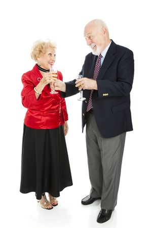 Senior man at a holiday party handing his beautiful wife a glass of champagne.  Full body isolated on white. photo