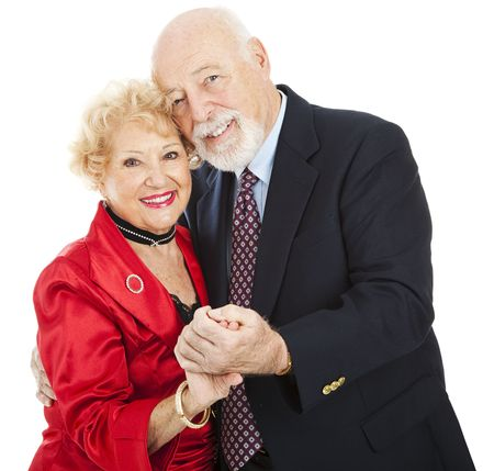 Beautiful senior couple in love, dancing cheek to cheek.  Isolated on white.