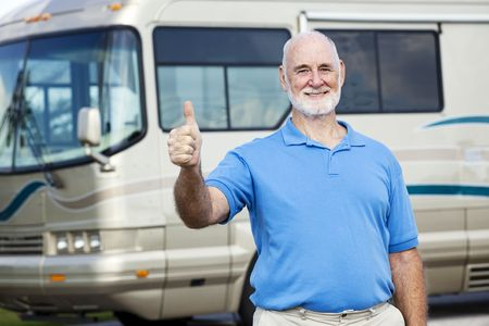 Senior man in front of his luxury motor home gives the thumbs up sign.