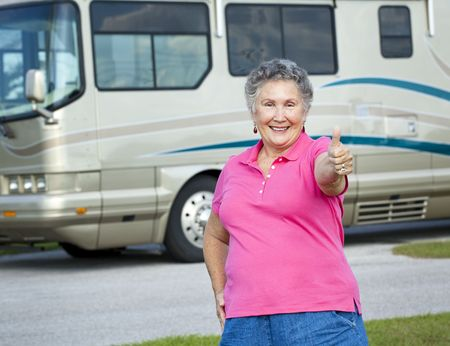 Happy senior woman standing in front of her luxury motor home, giving the thumbs up sign.   photo