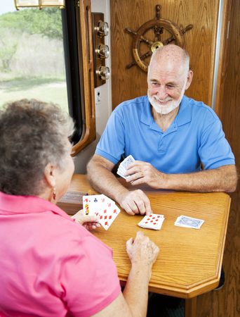 Retired senior couple playin a game of cribbage in the kitchen of their motor home.   photo