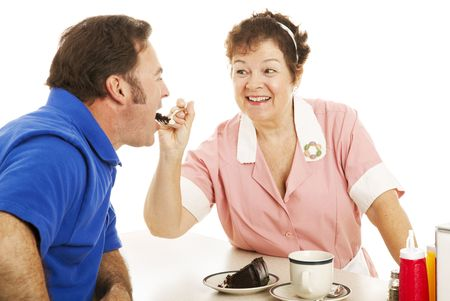 Flirty waitress feeding chocolate cake to her customer.  White background. Stock Photo - 5662574