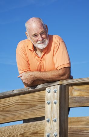 Portrait of a handsome, fit senior man leaning on a wood railing.   photo