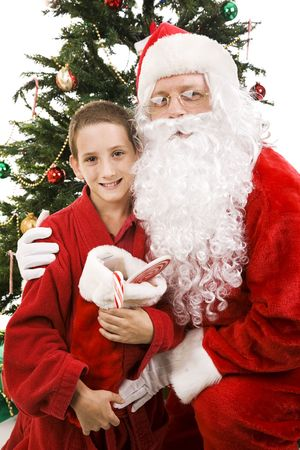 Santa gives a hug to a cute little boy by the Christmas tree.   Stock Photo