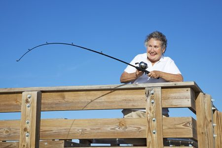 Retired senior woman on a pier in Florida, reeling in a big fish.