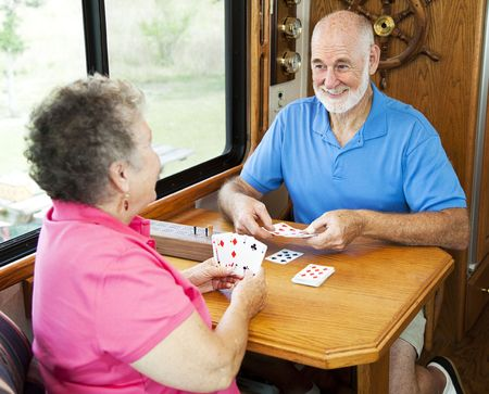 Senior couple vacationing in their motor home, playing a game of cribbage.   photo