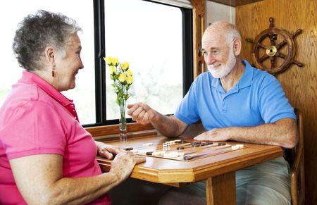 Senior couple playing backgammon in the kitchen of their motor home.