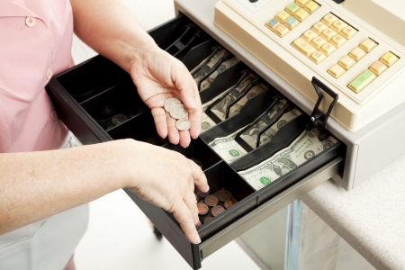 maquina registradora: Primer plano de las manos de un cajero hacer el cambio de un registro completo en efectivo.