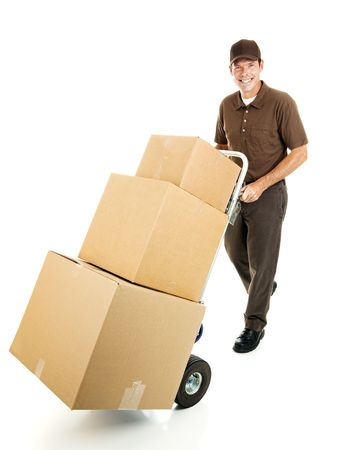 Friendly delivery man or mover pushes a stack of boxes on a hand truck.  Full body isolated.