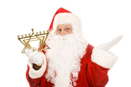 chanukah: Santa Claus holding a Jewish menorah and looking confused.  Isolated on white.