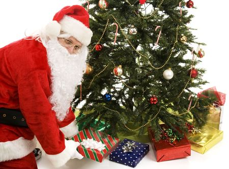 Santa Claus puts presents under the Christmas tree.  White background. 写真素材