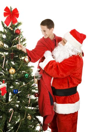 Santa lifting adorable little boy to take a candy cane off the Christmas tree.  White background. Stock Photo - 5835624