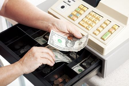 Horizontal view of an open cash register drawer asa a cashier makes change. Stock Photo - 5852003