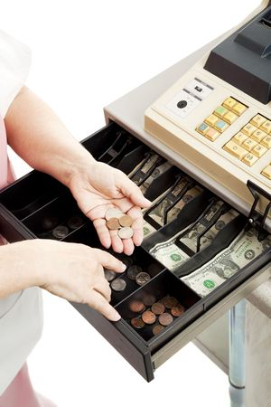 Closeup of a cashiers hands making change in a cash register drawer.  Vertical view, white background.