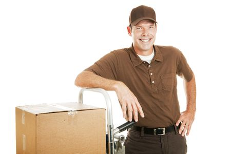 Handsome delivery man leaning on his dolly filled with boxes.  Isolated on white. photo