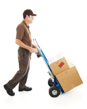 Full body side view of a delivery man or mover carrying boxes on a hand truck.  Isolated photo