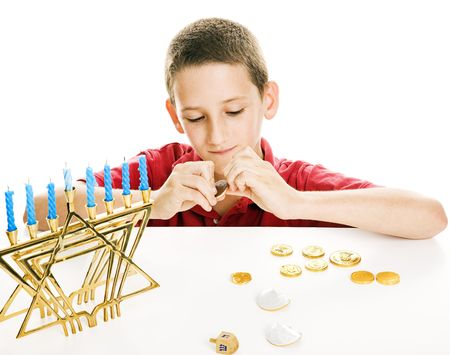dreidel: Little boy playing with his dreidel and eating chocolate coins on Chanukah.  White background.   Stock Photo