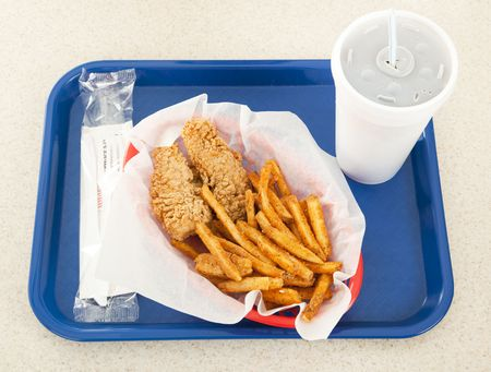 Fast food tray holding a basket of fried chicken, french fries, and a styrofoam cup of soda.   Stock Photo
