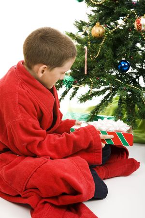 Little boy opening a Christmas present under the tree. White background. Stock Photo